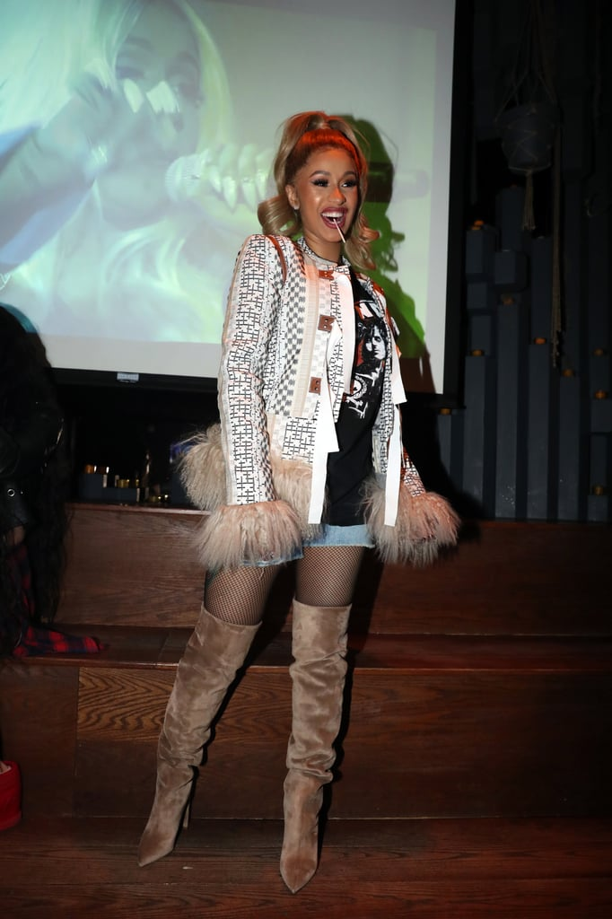 Wearing a fuzzy jacket with a denim skirt and thigh-high boots at a listening party for her album.