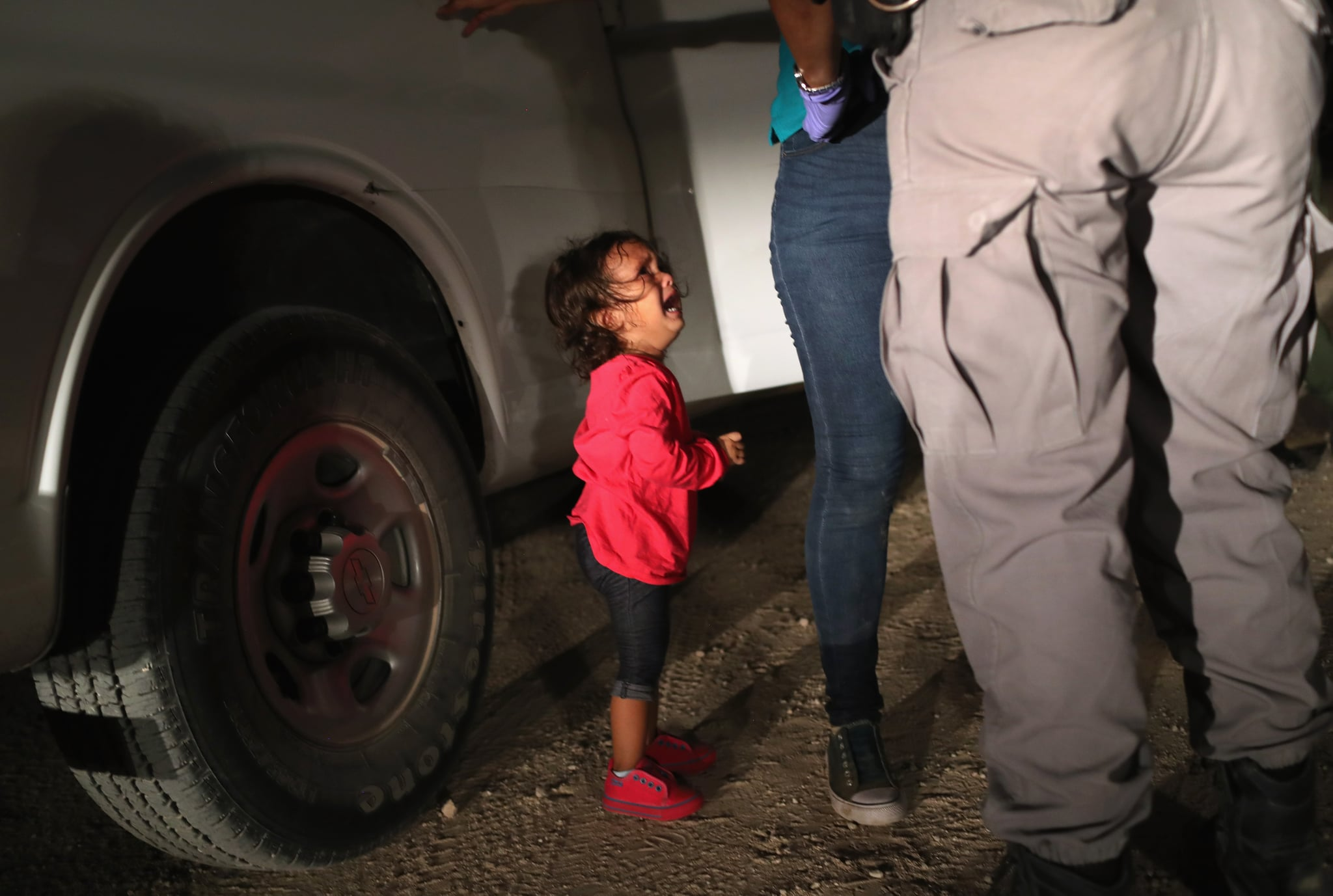 MCALLEN, TX - JUNE 12:  A two-year-old Honduran asylum seeker cries as her mother is searched and detained near the U.S.-Mexico border on June 12, 2018 in McAllen, Texas. The asylum seekers had rafted across the Rio Grande from Mexico and were detained by U.S. Border Patrol agents before being sent to a processing center for possible separation. Customs and Border Protection (CBP) is executing the Trump administration's
