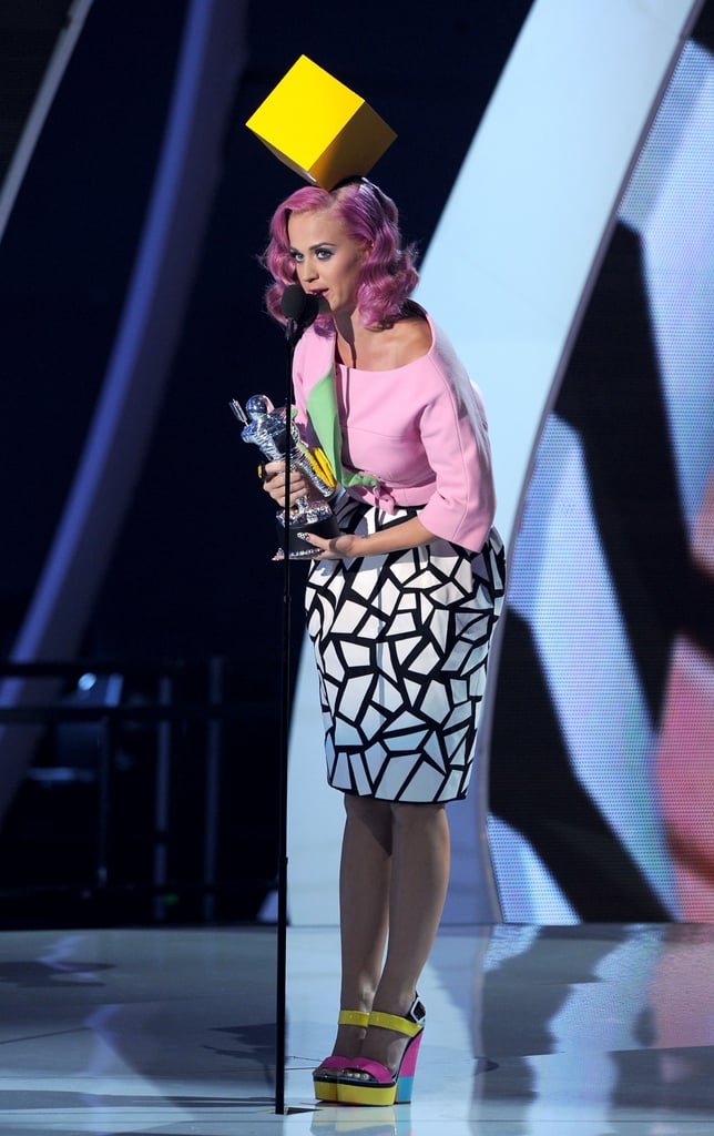 Katy Perry took to the VMAs stage wearing a pink top paired with a black and white mosaic print tulip skirt by Christian Dior, bright colorblock wedges by Giuseppe Zanotti, and the ultimate topper: a square yellow hat by Philip Treacy.
