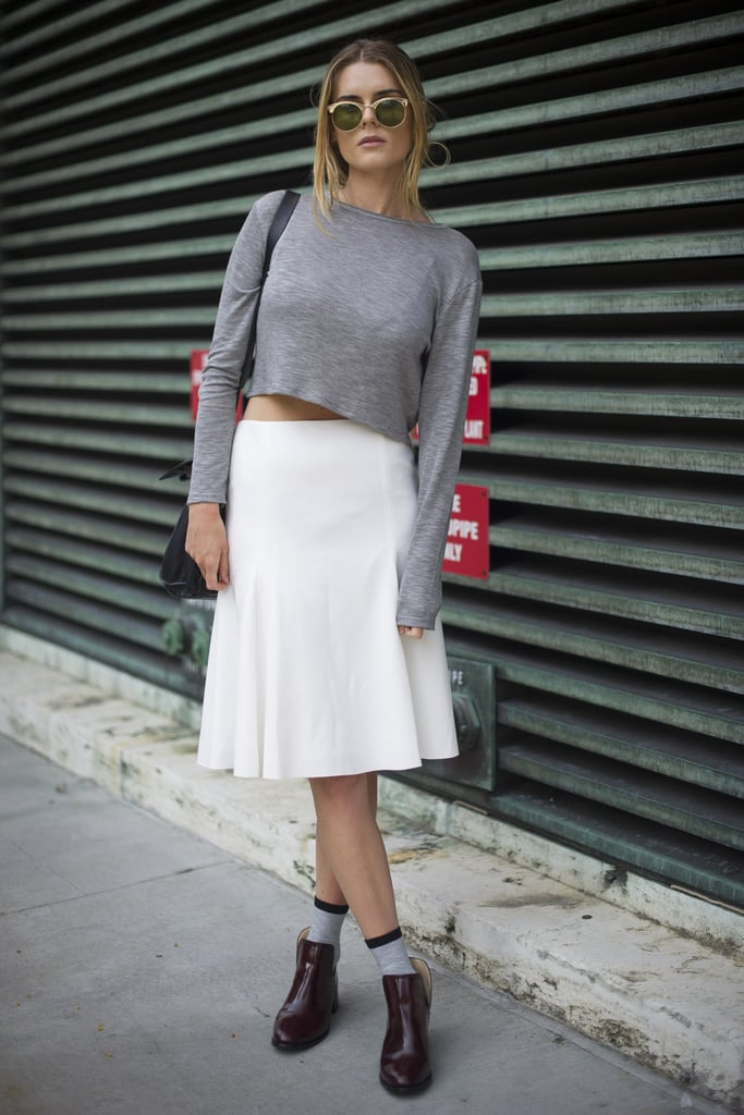Stay on trend in a high-waisted skirt and crop top, but keep your footwear practical with a pair of patent booties.