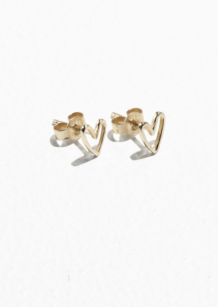 """أقراط كبس فضيّة مطليّة بالذهب على شكل قلب – يمكنكِ شراؤها من علامة """"آند أذر ستوريز"""" (بسعر 99 درهماً إماراتيّاً)"""