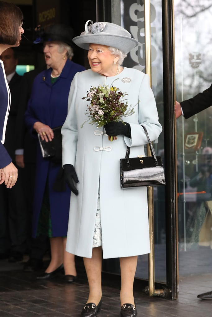 In February 2018, Queen Elizabeth was spotted in a light blue ensemble, which she accessorized with a black Launer handbag, matching gloves, and, of course, her black loafers.
