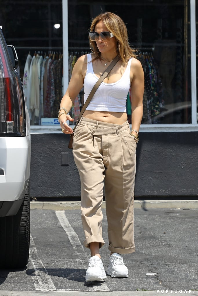 """For Jennifer Lopez, what's old is new again — not only when it comes to romance, but her closet, too. While shopping with her daughter, Emme, in Los Angeles on Tuesday, the singer wore an outfit that brought us back to the early aughts: low-rise khaki pants featuring an asymmetrical crisscross waistline and a ribbed crop tank. Well, if anyone can refresh khaki pants and a slouchy silhouette, it's J Lo.  And of course, in true J Lo fashion, she casually bared her abs, pairing the cropped and low-rise combo with a Coach x Jean-Michel Basquiat purse and The Kooples Tomorrow sneaker. She effortlessly accessorized with her signature oversize sunglasses, hoops, and stacks of gold and silver jewelry. If you ever feel ready to wear cargo pants again, J Lo's recent outfit is certainly one to save for inspiration. Ahead, see how the star styled her nostalgic pieces for a low-key outing.       Related:                                                                                                           Ben Affleck's OG """"Bennifer"""" Outfits Are a Total 2000s Vibe"""