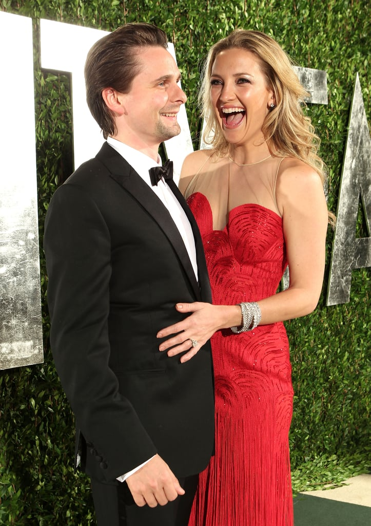 Kate Hudson and her fiancé Matt Bellamy posed outside last night's Vanity Fair Oscars bash. The couple skipped out on attending the Oscars show, but met up with friends to let loose afterward. Kate and Matt said hello to some of their pals like Cameron Diaz, Gwyneth Paltrow, and more at the magazine's bash held inside the Sunset Tower. Kate picked a bright red Versace gown for the occasion and added a bit of color next to Matt's dapper black-and-white tux.