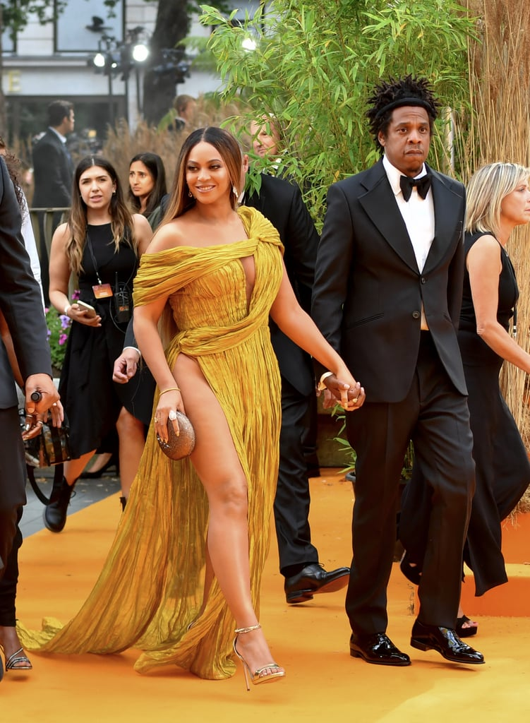 Leave it to Beyoncé to show up to the Lion King UK premiere in London looking like an actual golden goddess. The 37-year-old singer, and voice of Nala, walked hand-in-hand into the showing with her husband JAY-Z wearing a drop-dead gorgeous dress. Queen Bey stunned in an off-the-shoulder gown, complete with sexy hip-high slit and a train fit for royalty. Seems pretty appropriate, since she rubbed elbows with Prince Harry and Meghan Markle behind-the-scenes.  She tied the look together with metallic silver heels and a neutral clutch, while JAY kept things classic with a sophisticated black tux. Keep reading to see more photos from their glamorous night out. We like to think Meghan had plenty of compliments to give Beyoncé over this jaw-dropping ensemble.