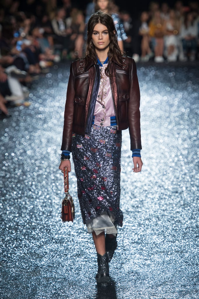 Kaia Walked in the Coach Show in a Leather Jacket and Shimmering Midi Skirt