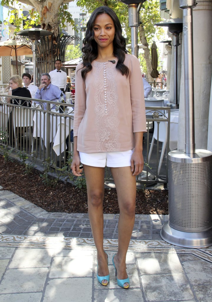 Zoe Saldana was dainty in a pair of white shorts and a dusty rose lace blouse, both by Dolce & Gabbana, which she punched up with turquoise peep-toe pumps.