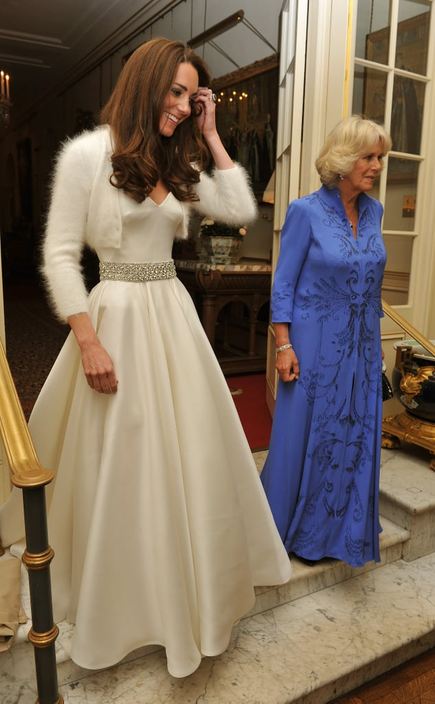 "Kate Middleton was in a second white gown designed by McQueen's Sarah Burton this evening as she left Prince Charles's official London residence, Clarence House, on the way to the big party at Buckingham Palace. Kate Middleton's wedding dress lavishly featured hand-embroidered lace and a nearly nine-foot-long train, but this number was strapless in satin, with diamante embroidered detail around the waist. Kate also paired the piece with an angora bolero! Kate, the new Duchess of Cambridge, left Clarence House with her husband, William, as well as her father-in-law, Prince Charles, and mother-in-law, Camilla. Camilla was in another get-up as well, wearing her second Anna Valentine of the day. The foursome took off for the palace, where Charles is hosting a 300-person private dinner. Charles is due to give a toast, as will Kate's dad, Michael. Queen Elizabeth won't attend the party, which is expected to go into all hours of the night since Buckingham Palace has no closing time! Prince Harry and Pippa Middleton organized dancing for the guests and ensured that there will be food, like bacon sandwiches, for the ""survivors"" who make it until 6 a.m. Kate and William aren't expected to stay up that late, as they're leaving for their honeymoon tomorrow!"