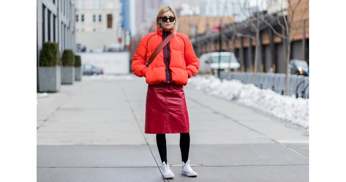 With An Orange Puffer Jacket A Red Leather Skirt And Black Tights