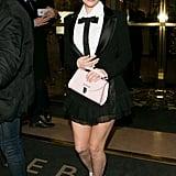 مرتديةً زيّاً من تصميم فالنتين يوداشكين مع حذاء كعب عالٍ من Casadei، وحقيبة من علامة Cambridge Satchel Company.