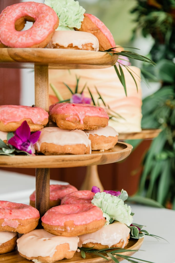 "When thinking about wedding desserts, the most obvious ones that come to mind are cake and cupcakes. However, this wedding season, doughnuts are taking over the dessert table. According to Pinterest's annual trend report, searches for ""doughnut decor"" are up 748 percent in 2019.  It's no wonder why: these unassuming yet delicious sweet treats are sure to bring a smile to any wedding guest's face. Not to mention they can be gorgeously decorated and displayed to go with any wedding decor. There are so many creative ways to shape a doughnut, too — you can create interesting designs or spell out a name or word. Oh, and did we mention the best part? They're crazy-affordable compared to ornate tiered cakes and other traditional (read: overpriced) wedding desserts. See how couples dress up and display their wedding doughnuts ahead. If you want some inspiration on how to incorporate doughnuts into your wedding (or just want to look at aesthetically pleasing food pics), then check out these drool-worthy doughnuts now.      Related:                                                                                                           17 Unforgettable Wedding Trends to Wow Your Guests in 2019"