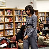 The FLOTUS never disappoints on the accessories front, and this latest take on a belted look is proof. She chose a subdued Narciso Rodriguez suit for a school visit in Chicago in early April, but punched it up with a metallic reptilian-textured belt.