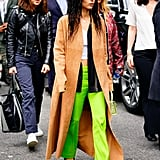 Yes, slime green can look this cool. Zoë styled her slacks with a men's striped shirt worn undone and oversize over a lace camisole, and a long suede duster. She accessorized with a covetable croc-effect By Far bag in sage.