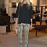 Poppy Delevingne worked casual style in a grey jumper, mottled jeans, gold sandals and a tasseled handbag at KaDeWe in Berlin.