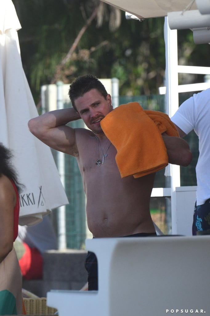 Stephen Amell jetted off to St. Barts for a Christmas family vacation with his wife, Cassandra Jean, and their 2-year-old daughter, Mavi Alexandra Jean Arnell. The Arrow star showed off his impressive shirtless body while braving the chilly water for a dip in the ocean before heading back to shore to play with his little one and adding to his series of cute family moments. The 34-year-old Canadian hunk currently stars on the hit TV show Arrow alongside Emily Bett Rickards, who hit the beach in Hawaii earlier this month. On top of heating up the screen with his character Oliver Queen's intense relationship with Emily's Felicity Smoak, Stephen has definitely captured the audience's attention with his smoldering good looks. Scroll through to see more of Stephen's toned physique, and then check out his hottest moments.