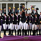 Zara Phillips stands among her teammates after winning the silver medal in an equestrian event.