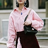 Layer up with a pink shirtdress and side-slit burgundy skirt on top.