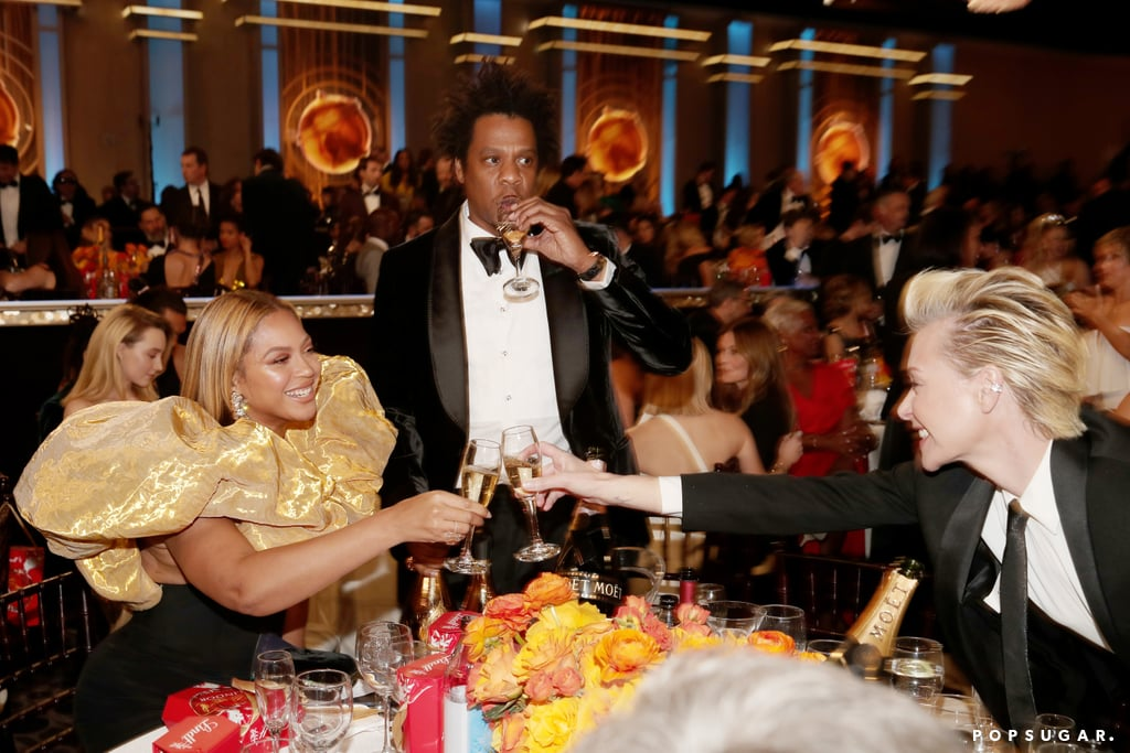 """In an unexpected yet highly appreciated turn of events, Beyoncé and JAY-Z stepped out for the Golden Globes on Sunday. Although the power couple wasn't photographed on the red carpet, viewers were shocked to see them among the crowd as Kate McKinnon presented Ellen DeGeneres with the Carol Burnett Award. While Bey wore a voluminous black-and-gold ensemble, Jay sported a tuxedo. The couple celebrated in true star fashion, bringing their own bottles of Armand de Brignac Champagne to the ceremony. Inside, they mingled at their table with Ellen and her wife, Portia de Rossi, as well as Jennifer Lopez, and sipped on their bubbly. Fun fact: JAY-Z actually bought Armand de Brignac in 2014.  The pair attended the event in support of Disney's reboot of The Lion King, which was nominated for best animated film. Beyoncé's song """"Spirit"""" — which is featured on her LP The Lion King: The Gift — also earned a nod in the best original song category. Bey and JAY reportedly arrived late (according to attendee and film critic Cameron Bailey, they """"just materialized""""), but perhaps everyone else was just early? At any rate, it's not the appearance we anticipated, but it's the appearance we deserve. Look ahead to see the duo at the ceremony!      Related:                                                                                                           The Red Carpet Looks at the 2020 Golden Globes Are Everything We Want and More"""