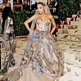 """At the May 7 Met Gala, Ariana accompanied Vera Wang in a watercolour strapless gown the designer created. Appropriate for the event's """"Heavenly Bodies"""" theme, the piece was painted with Michelangelo's """"The Last Judgment"""" scene, which covers the altar wall of the Sistine Chapel in Vatican City. Ariana's momentous look was finished with a large tulle bow and Butani jewels."""