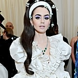 Lily Collins's Lilac Eye Shadow and Floral Hair Accessories at the Met Gala