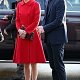 For a visit to the McBride Museum, Kate covered up in a cherry-red Carolina Herrera coat.