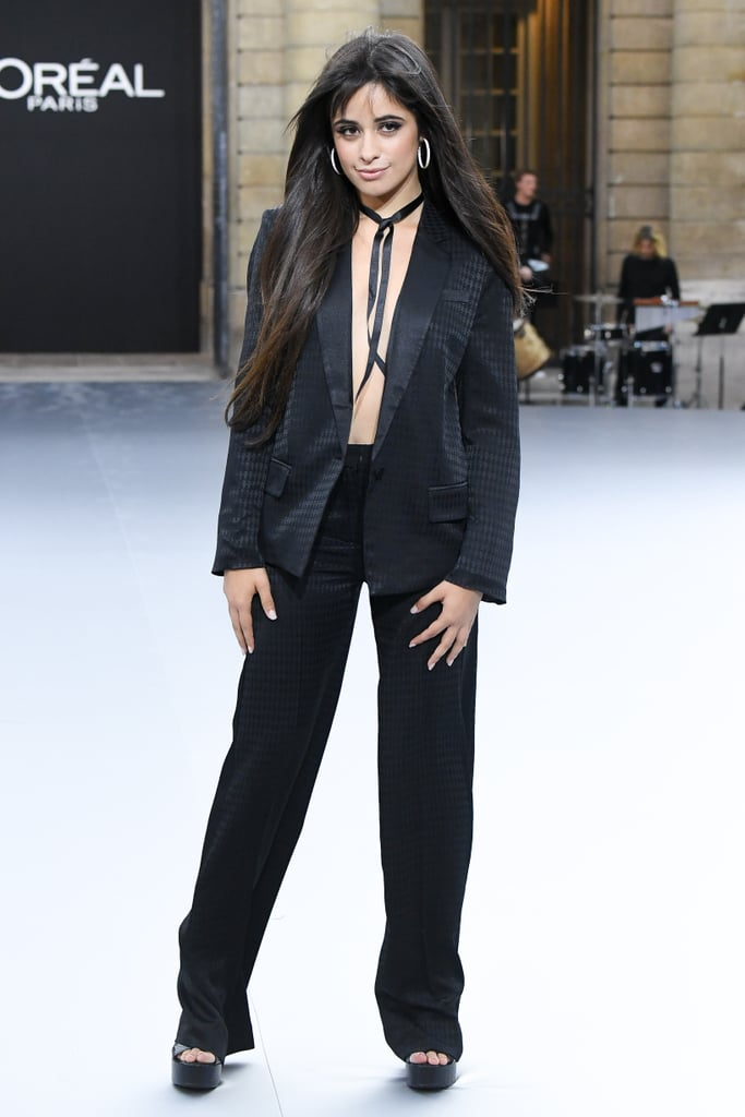 "Camila Cabello absolutey brought the sapphire moonlight with her when she made her runway debut at the Le Defile L'Oreal Paris fashion show during Paris Fashion Week on Sept. 28, and who knew pantsuits could be so sexy? Yep, the queen of the oversized tye-dye hoodie swapped her street clothes for a stylish, textured blazer, straight black pants, and chunky heels for a look that's basically the definition of a power suit — no top necessary. To accessorise her look, Camilla went with white hoop earrings, a matching white manicure, and black ribbon necklace to tie everything together. The 22-year-old ""Señorita"" singer wasn't afraid to laugh and wave to the audience as she strutted alongside her fellow models, having fun with her first runway experience and coming away with an important message for her fans. ""Genuinely had SO much fun walking for the first time in a runway show with these strong and inspiring women last night — they were so kind, so funny, and so beautiful inside and out!"" she captioned an Instagram post after the show. ""This was my first fashion show and I'm so grateful it was with L'Oréal where the definition of beauty has nothing to do with what you look like and everything to do with how beautiful you feel.  Camila went on to point out that beauty is diverse and that self-worth isn't determined by physical attributes. ""Beauty comes in all shapes, sizes, colours, and ages. Obviously I remember hearing 'because you're worth it' in commercials since I was young, but as I'm finding my way and becoming a woman, I realise how important that phrase really is — to remind yourself that you're worth asking for what you need, fighting through life's obstacles and challenges and struggles. You're worth battling fears and doubts because you're worth it — and you're worthy of happiness, and love, and everything good."" See more photos of her stunning pantsuit and fantastic runway strut ahead."