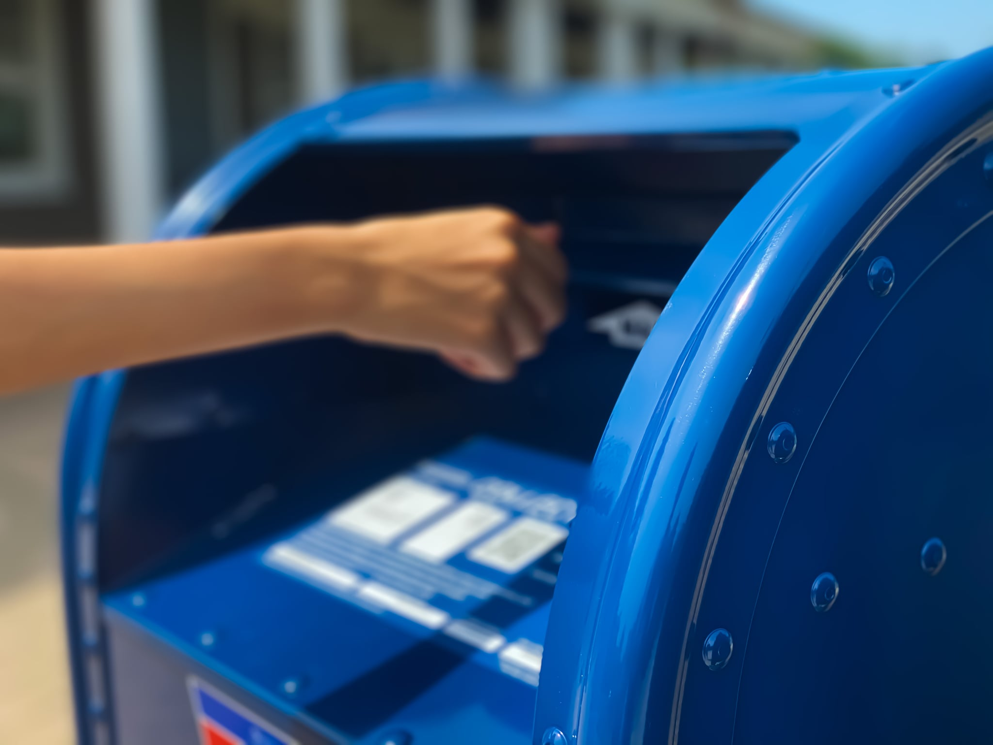female mailing letter at outdoor mailbox
