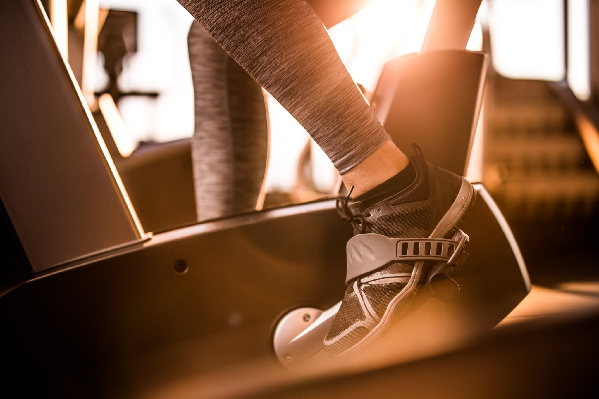 Close up of athletic person exercising on exercise bike in a gym.