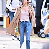 While shooting a movie, Selena was spotted wearing a simple pink tank top with step-hem jeans and a beige trench coat.