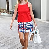 Reese Witherspoon matched a red tank with a printed skirt, both by Kate Spade Saturday, then finished with white sandals and a matching bag.