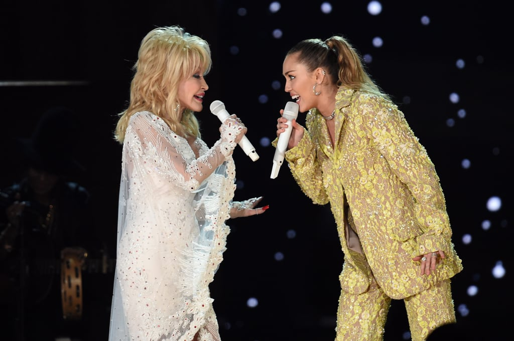 "Dolly Parton had her goddaughter Miley Cyrus by her side for her Grammys tribute on Sunday night. During the star-studded performance, the legendary country singer shared a special moment with Miley as they sang her hit song ""Jolene."" The two put their sweet bond on display as they sang to each other, shared a few laughs, and showed off their insane star power. Miley certainly lived up to her ""smiley"" nickname during the performance as well — she couldn't stop grinning at her famous godmother. Same, Miley."