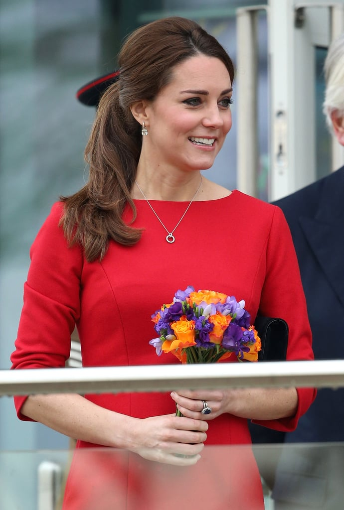 The Duchess of Cambridge showed a hint of her baby bump on Tuesday when she arrived at Norfolk Showground in Norwich, England, to attend a fundraising launch for East Anglia's Children's Hospices. Kate Middleton wore a red Katherine Hooker dress, which she paired with black heels. While her outfit was perfectly business appropriate, the dirt-covered paths outside the showground proved to be difficult to maneuver in Kate's pumps. Despite this, Kate continued with her royal work, even stopping to greet a group of children who were waiting to give her a bouquet of flowers. She'll be meeting with other children and families throughout the day to hear about their experiences with the hospice charity. The East Anglia's Children's Hospices is a cause close to Kate's heart as she has been a patron of the organization since 2012. Her appearance this week is to launch a $15.6 million fundraising effort, which will raise money for a new hospice and other expenses within the charity.  It's been a busy time for Kate, who just last Wednesday attended a charity gala for another one of her favorite charities, Place2Be, at Kensington Palace. Things won't be slowing down any time soon as Kate and Prince William are slated to visit NYC and Washington DC from Dec. 7 through Dec. 9. The pair's visit — which is both of their first time visiting the two American cities in any capacity — is not an official royal tour and is, instead, meant to be on behalf of their various charities.