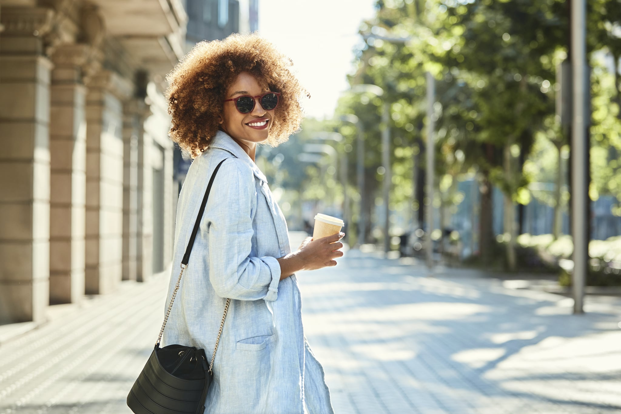 Portrait of smiling young woman holding disposable coffee cup. Beautiful female is with purse walking on sidewalk. She is wearing casuals in city.