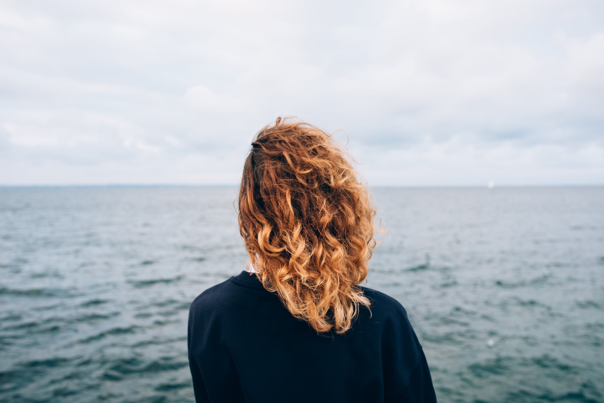 Female with red curly hair outdoors standing alone thinking near blue water. Rear view of young woman looking at sea.