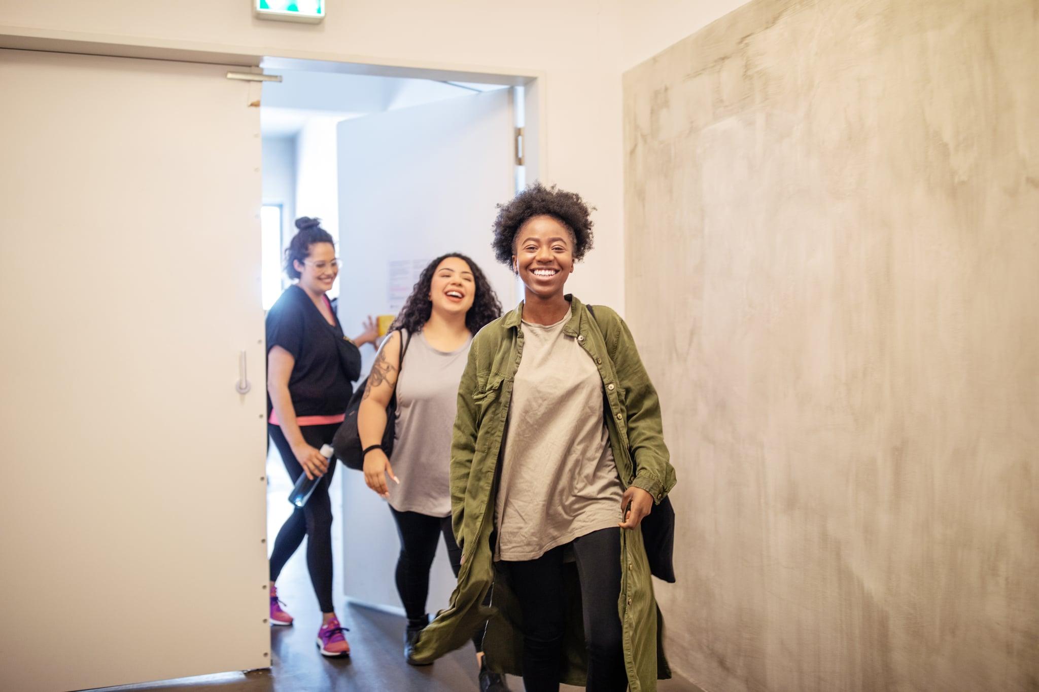 Group of multiracial females entering fitness studio. Smiling women walking through a doorway in dance class.