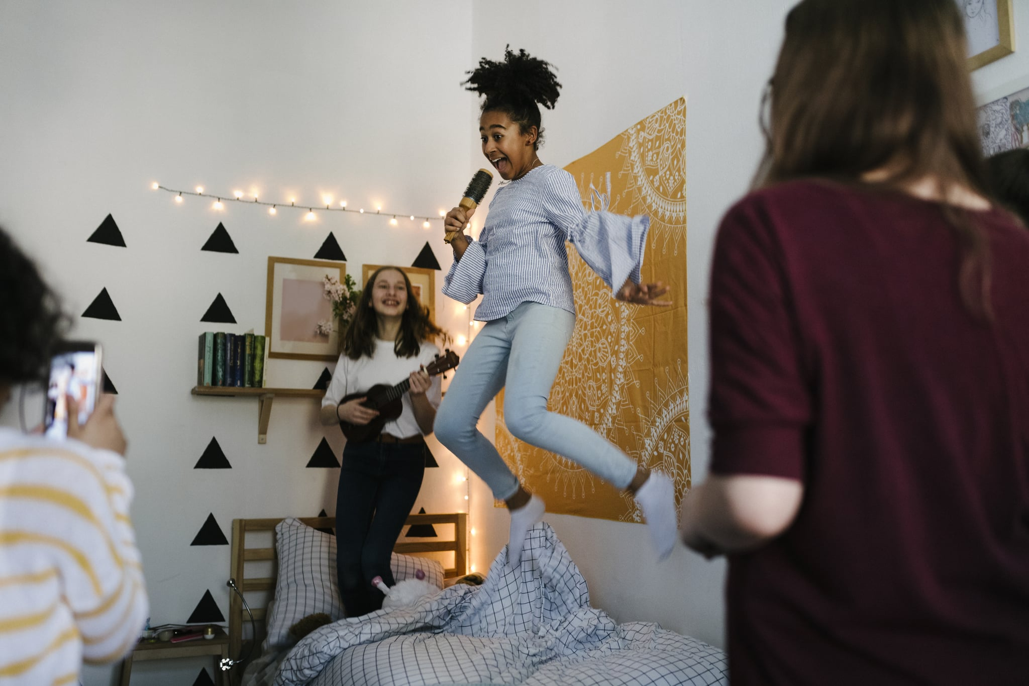 Black tween jumping in the air while singing into hairbrushes at slumber party.