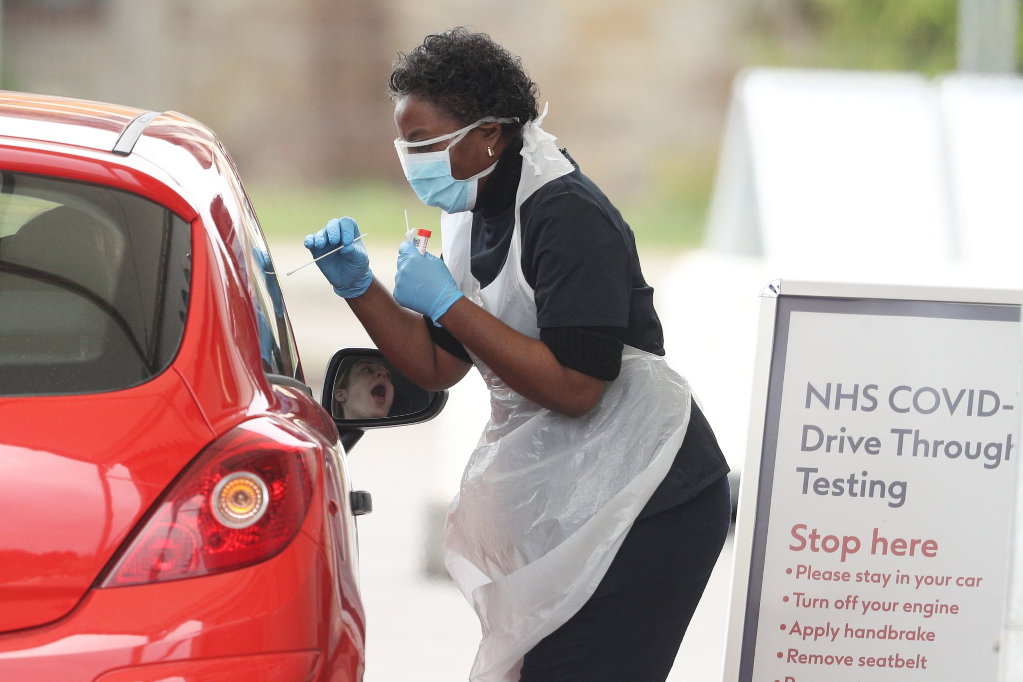 CHESSINGTON, UNITED KINGDOM - MARCH 30:  A nurse takes a swab at a Covid-19 Drive-Through testing station for NHS staff on March 30, 2020 in Chessington, United Kingdom. The Coronavirus (COVID-19) pandemic has spread to many countries across the world, claiming over 30,000 lives and infecting hundreds of thousands more. (Photo by Dan Kitwood/Getty Images)