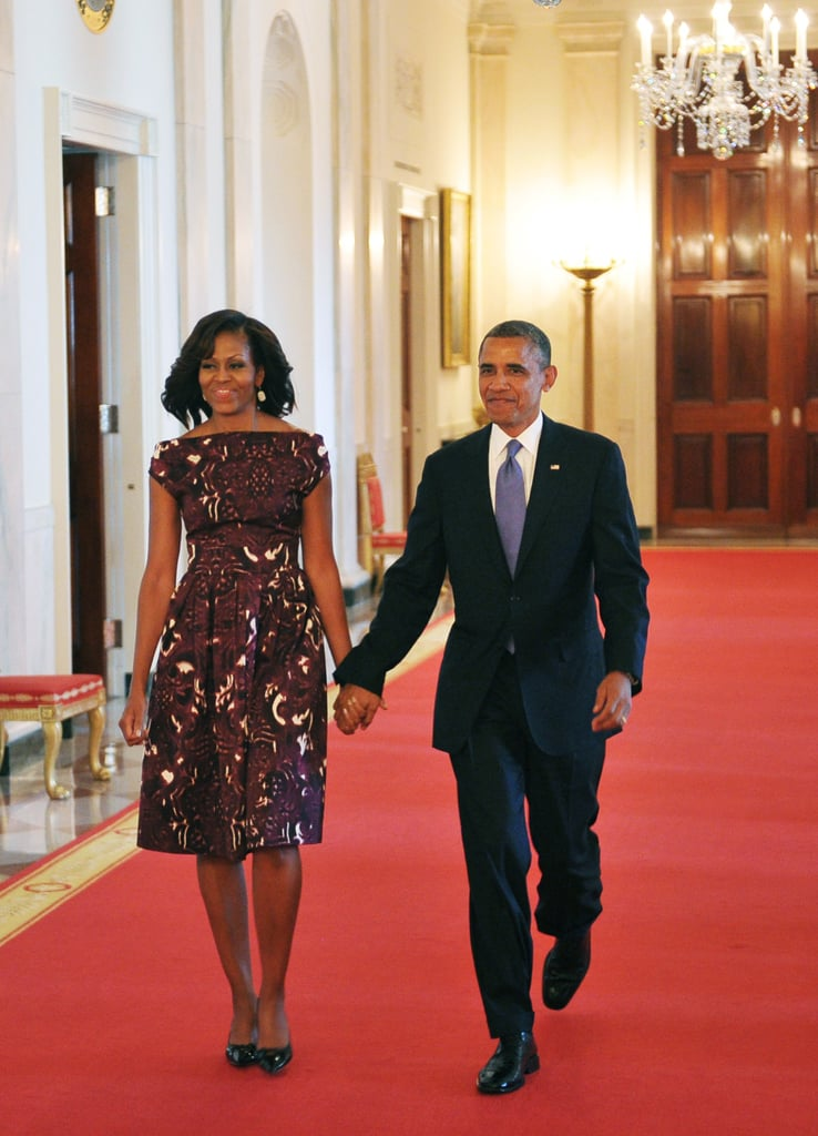 Michelle went for a boatneck dress sporting and intricate deep red and white pattern when she accompanied her husband to the National Medal of Arts and National Humanities Medal presentation ceremony.