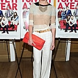 Hilary Rhoda balanced fancy with casual in white trousers, a colorblock sweater, and a bright red clutch at the I Give It a Year screening in NYC.