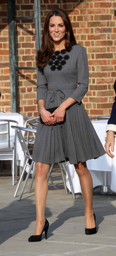 Kate wearing her grey Orla Kiely dress in 2012, accessorised with black pumps, a simple clutch, a dainty diamond bracelet, and her sapphire engagement ring.