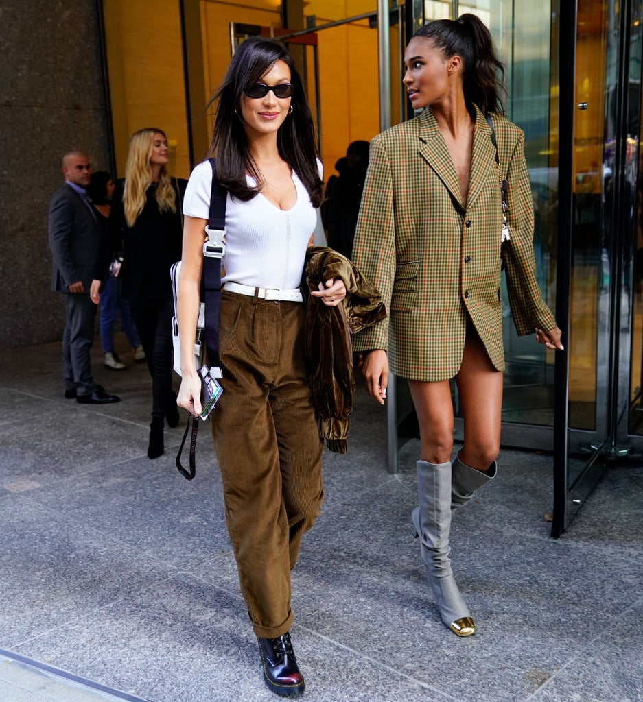 32d026cd519 Bella Hadid wearing a white top with brown suede pants and tiny sunglasses. Cindy  Bruna
