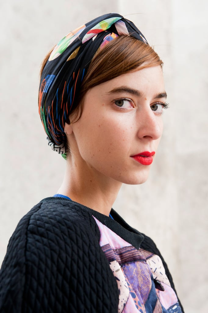 Polished, sideswept bangs tucked under a scarf look extra chic when paired with a bright red lipstick.