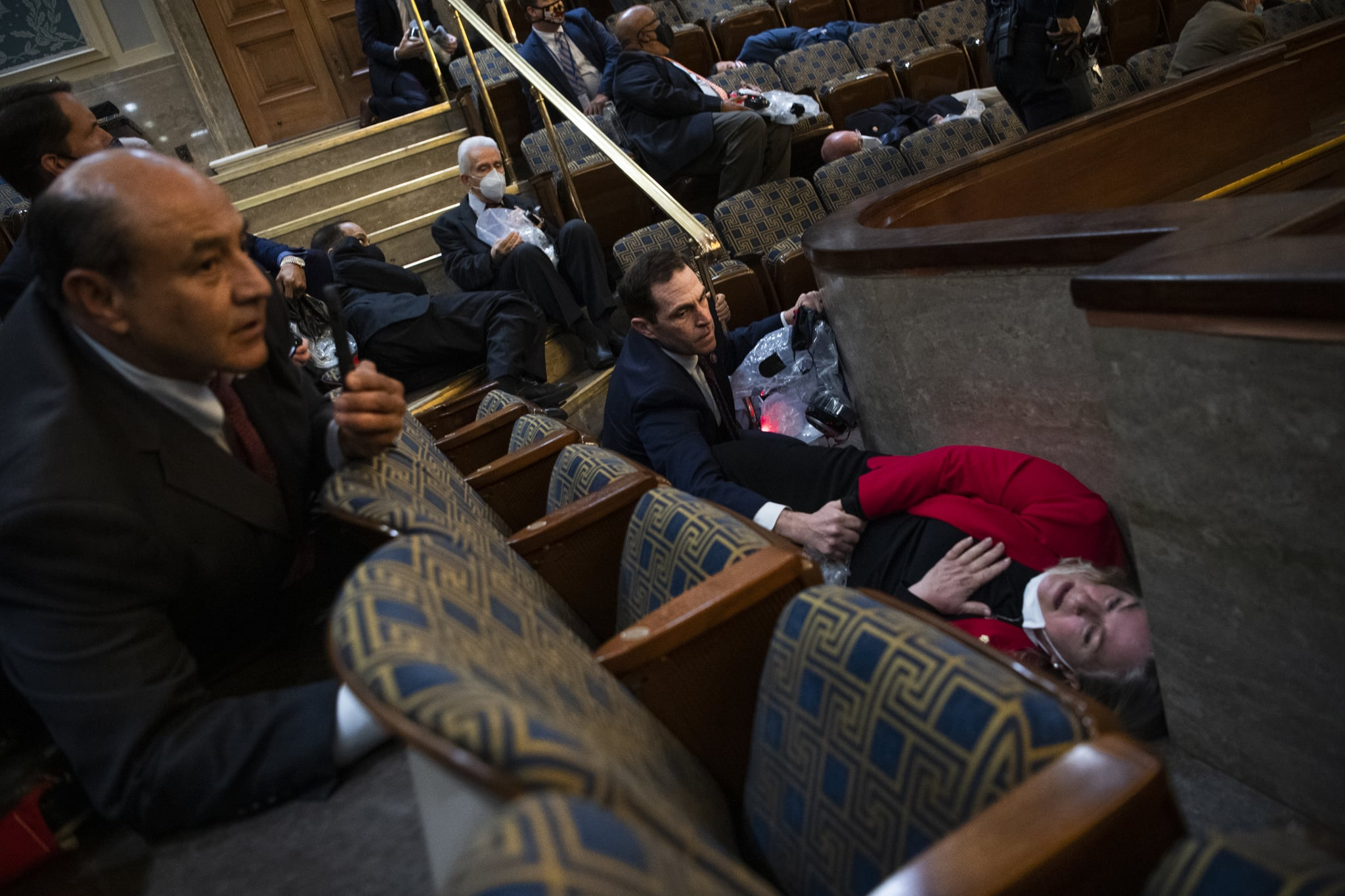 UNITED STATES - JANUARY 6: Rep. Jason Crow, D-Colo.,  comforts Rep. Susan Wild, D-Pa., while taking cover as protesters disrupt the joint session of Congress to certify the Electoral College vote on Wednesday, January 6, 2021. (Photo By Tom Williams/CQ-Roll Call, Inc via Getty Images)
