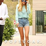 What does Bella wear for a snack run? The hottest Summer shoes. She paired her tall gladiator sandals with laid-back jean shorts, a mint sweater, and mirrored aviators.