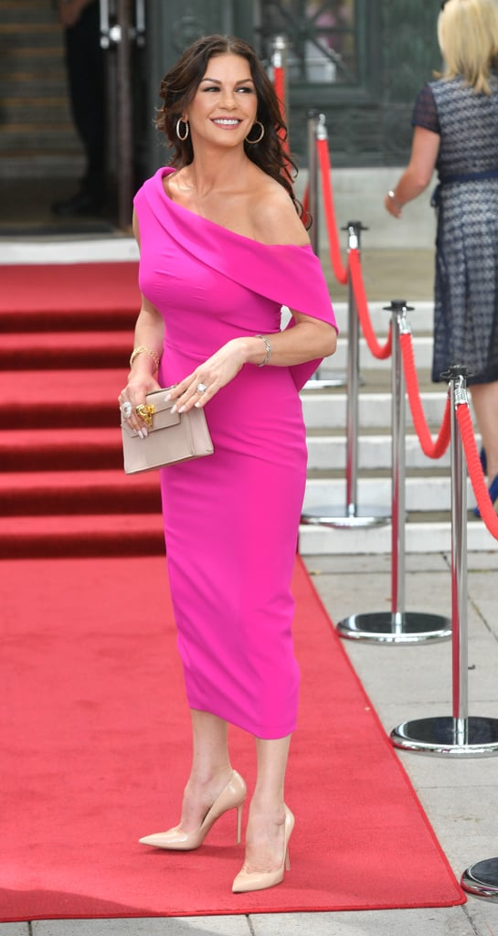 Catherine Zeta-Jones paid a visit to her hometown of Swansea, Wales, on Wednesday, when she was honored with the Honorary Freedom of the City and County of Swansea. The actress was accompanied by her husband, Michael Douglas, and her 18-year-old son Dylan for the important occasion, but she made sure all eyes were on her as she arrived at the city's Guildhall wearing a dramatic fuchsia dress. The dress featured an asymmetric neckline, which dipped off the shoulder on one side before draping around the body. She added a beige clutch bag with gold hardware, beige stiletto heels, and gold hoop earrings to complete the look. Keep reading to take a closer look at this killer dress from all angles. Catherine's worn some serious statement looks in the past, but we're convinced this one's right up there with the best.      Related:                                                                                                           Seeing Double? Catherine Zeta-Jones and Her 14-Year-Old Daughter Are Basically Twins