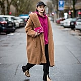 With a Cap, a Long Coat, a Hoodie, and Black Trousers