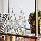 No detail is overlooked on the bar cart, from an acrylic tray holding colorful cocktail napkins to a bundle of striped straws.