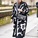 Work a bow-adorned style with a floor-length printed coat.