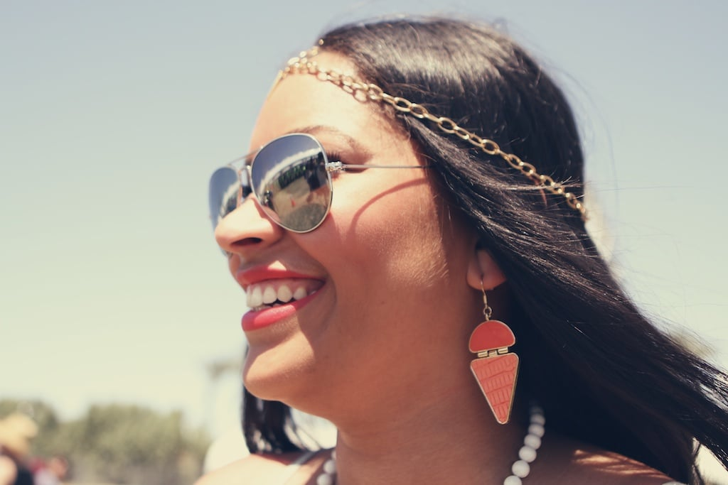 Reflective aviators, a chain headpiece, and statement earrings finish off this festive look.