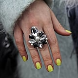 A statement ring popped against neon yellow nails.